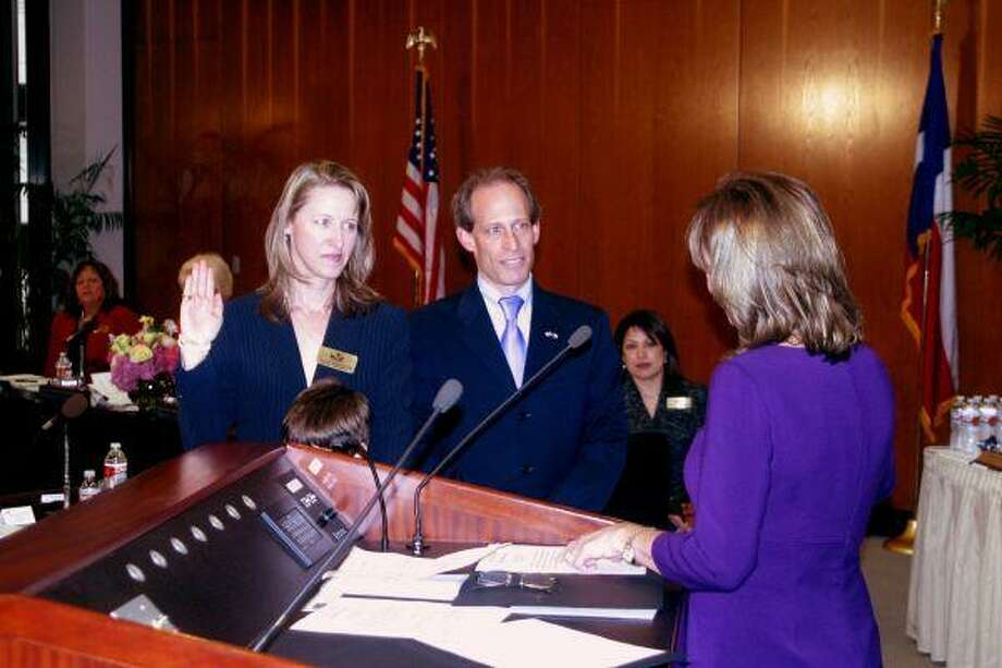 Sandie Meyers is sworn in as HCC trustee by State Sen. Joan Huffman, with husband and HISD Board President Greg Meyers at her side.