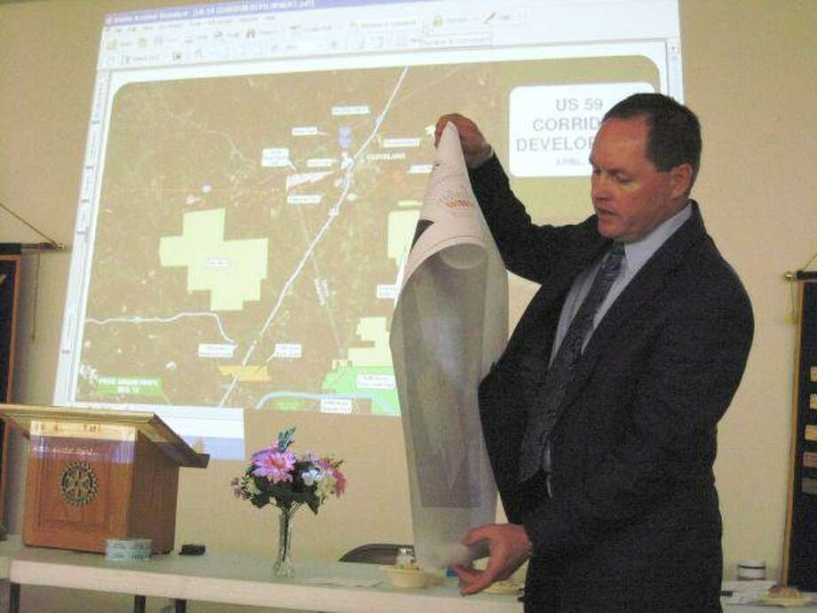 Tarkington real estate developer Scott Lambert unrolls a map of a planned development along US 59 just north of Cleveland. Lambert and Houston-based civil engineer Gary Montgomery discussed economic development at the Cleveland Rotary meeting on April 29.