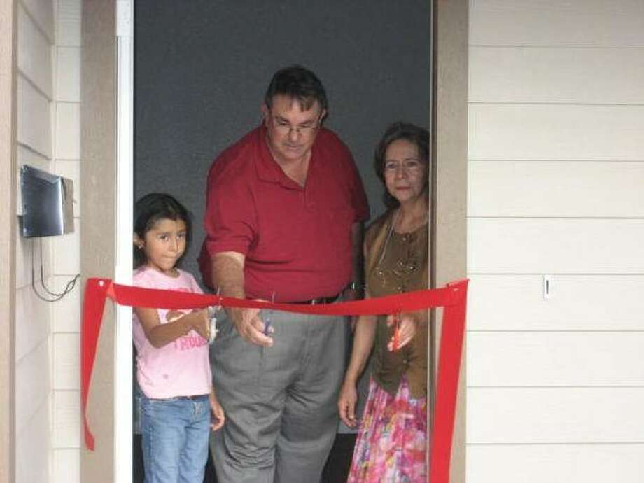 Thomas Hoffman, board president of Habitat for Humanity-Pasadena, joins Dora Arita and her granddaughter, Victoria, in cutting the ribbon on Habitat's 14th house at 1021 Witter. This is the second house in the new Second Harvest Subdivision. HFHP is currently working on a house at 1023 Witter, due to be completed in October. Anyone interested in volunteering, will find information at www.pasadenahabitat.org.
