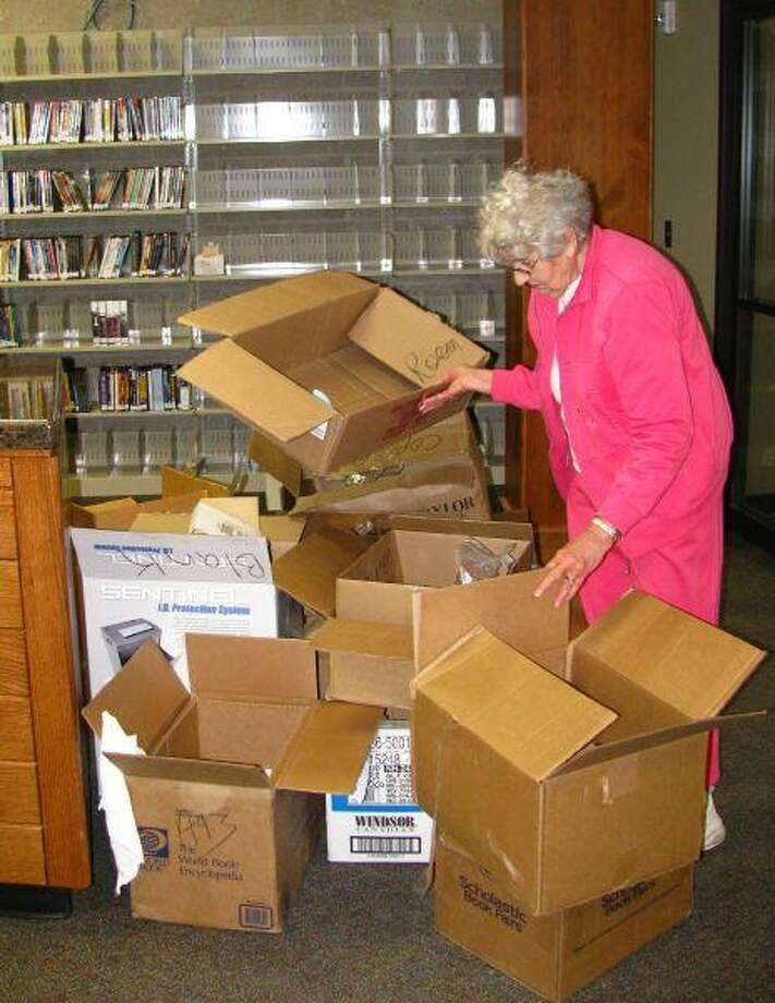 Jones Public Library's Rose Klimitcheck stacks empty boxes that were once filled with books. The books now fill the shelves at the library's new home at the Dayton Community Center.