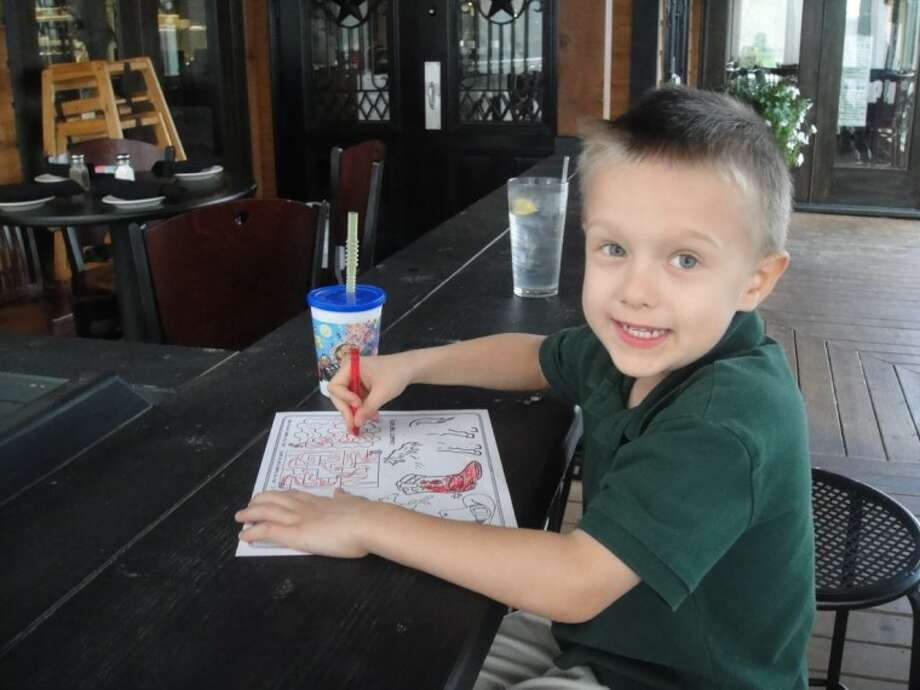 Kellum James Odom, 5, enjoys the coloring book/kids menu at Dekker's Mesquite Grill in Fulshear just outside of Houston.