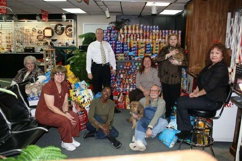 Employees of Pineforest Jewelry gather around the large pyramid of food donated by the store's customers to help feed the animals at the Houston SPCA.