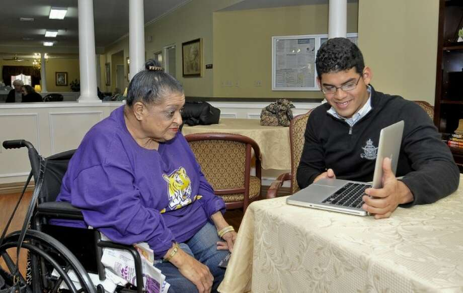 San Jacinto College student and PTK Alpha Gamma Zeta chapter president Ivan Quinones shows Park Manor South Belt resident Phyllis Lewis how to video chat using Skype. Photo: Andrea Vasquez