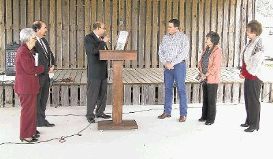 Juan Carreon, assistant vice president of public affairs for Union Pacific Railroad, center, presents Magnolia Mayor Todd Kana a proclaimation naming Magnolia an official Union Pacific Train Town on Tuesday afternoon. A ceremony was held to commemorate the occasion at The Depot in Magnolia. Pictured, from left, are Magnolia Historical Commission representative Celeste Graves, Greater Magnolia Chamber of Commerce chair Barry Tate, Carreon, Kana, Magnolia Councilwoman Anne Sundquist, and Magnolia Councilwoman Patsy Williams. Photo: Lindsey Vaculin / @WireImgId=2615212