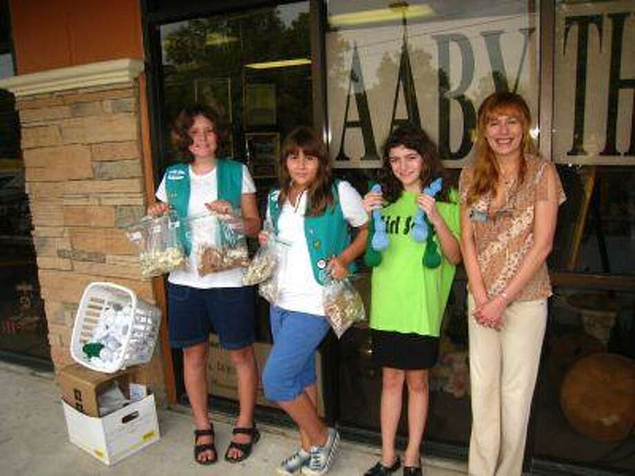 Girl Scout Troop 3308 earned its Bronze Award by volunteering at the AABY thrift shop and the Kingwood Kennels dog park. The troop is from Kingwood and the girls are students at Kingwood Middle School. From left are Mataia Styers, Lauren Brooks and Carley Sims with AABY founder Kay Pass. Not pictured are Grace Wilson, Katie Bonnin and Carissa Trevino.