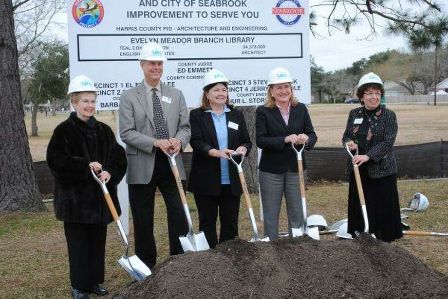 Lynn Meador Hall, Seabrook Mayor Gary Renola, Friends of the Library President Marianne Kolar, Harris County Commissioner Sylvia Garcia and Harris County Library System Director Rhoda Goldberg, from left, stop for a photo as they prepare to break ground for the new Evelyn Meador Library, which will replace the one destroyed by Hurricane Ike. Hall is the daughter of the late Evelyn Meador, for whom the library is named.