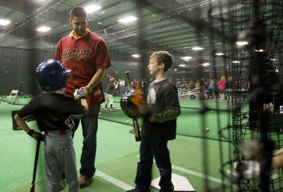 Houston Astros left fielder J.D. Martinez signs baseballs for children during a mini-training session with Oak Ridge Woodlands Area Little League baseball and SMCGSL softball players at The Edge sports complex in Spring. Photo: Staff Photo By Eric S. Swist