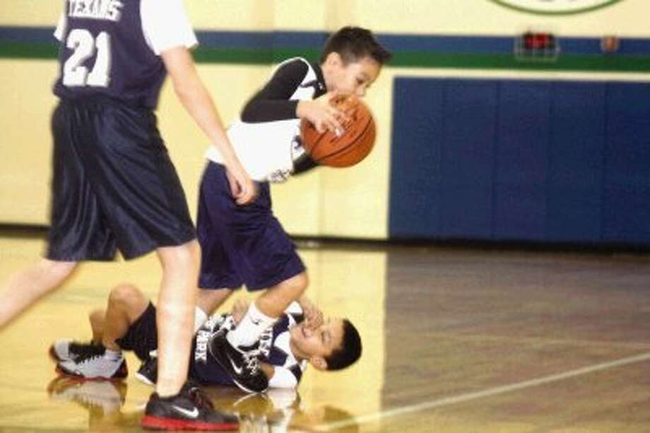 Heats player Andrew Gonzalez dribbles past a fallen Texans defender during Saturday's youth basketball game in the 10-and-under A division contest at Fairmont Junior High.
