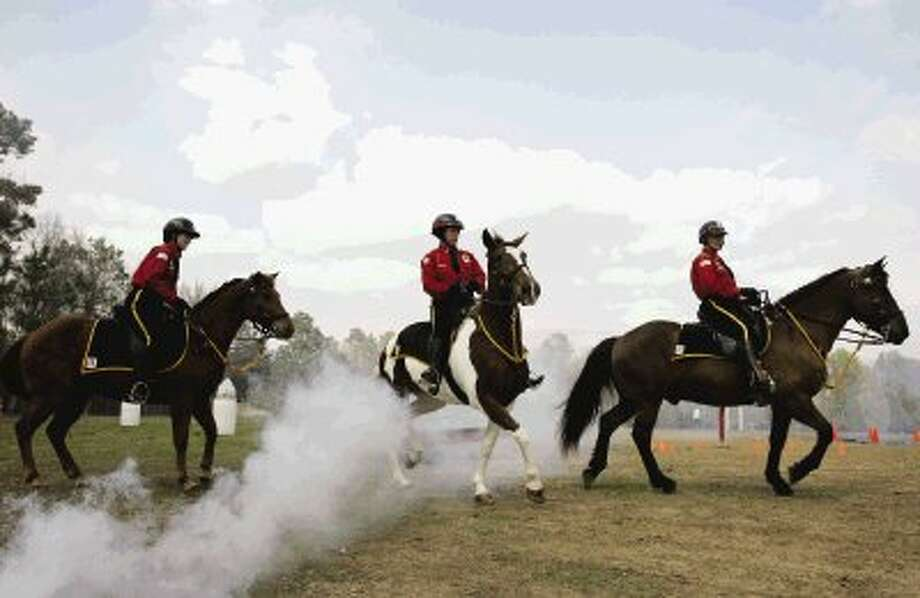 Troopers with Alpha & Omega Service Mounted Patrol maneuver their horses through a cloud of smoke during the sensory training demonstration portion of an obstacle course during the Class of 2011 Mounted Patrol Certification Academy graduation ceremony at the Willis AG Arena. The class graduated six new troopers as well as two police officers from the city of Keller Police Department and two officers from the city of West Monroe, La. / The Courier
