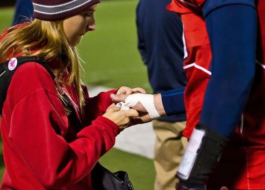 Dawson High School student athletic trainer Brittnie Smithley (left) helps to tape an athlete's injured hand. Photo: Pearland ISD