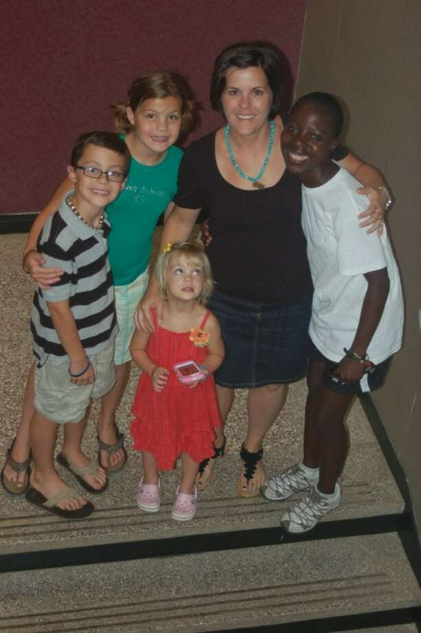 Kristen Welch and Maureen Owino pose with Welch's children (from left) Jon-Avery, 8, Madison, 11, and Emerson, 4. Owino and Welch founded Mercy House in September 2010, a nonprofit organization that provides a home to abused African women.