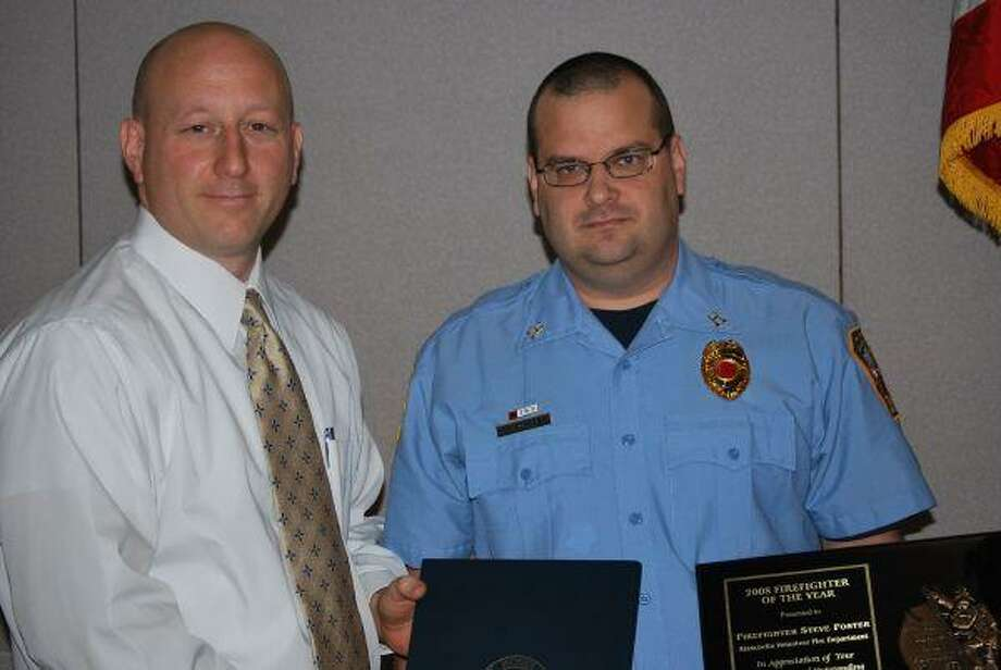 Photo by STEFANIE THOMAS/The ObserverHumble Area Chamber of Commerce Chairman of the Board Jason Medley presents the Fire Fighter of the Year Award to Capt. Steve Foster of the Atascocita Volunteer Fire Department.