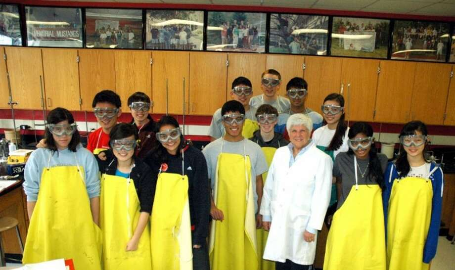 Karla Lowerre (in lab coat) with one of her AP Chemistry classes at Memorial High School. Group photos of previous classes ring the lab's walls. Photo: Rusty Graham