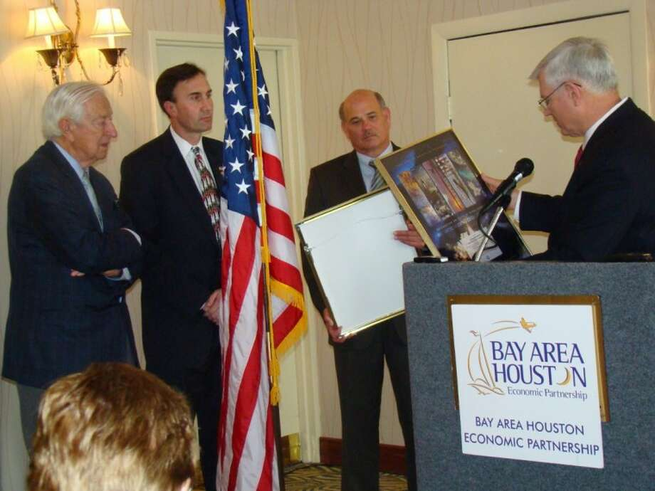 Johnson Space Center Director Mike Coats presents gifts to special guests at last week's Bay Area Houston Economic Partnership Aerospace Committee luncheon at the Hilton, Congressmen Ralph Hall and Pete Olson, from left, as BAHEP President Bob Mitchell looks on.
