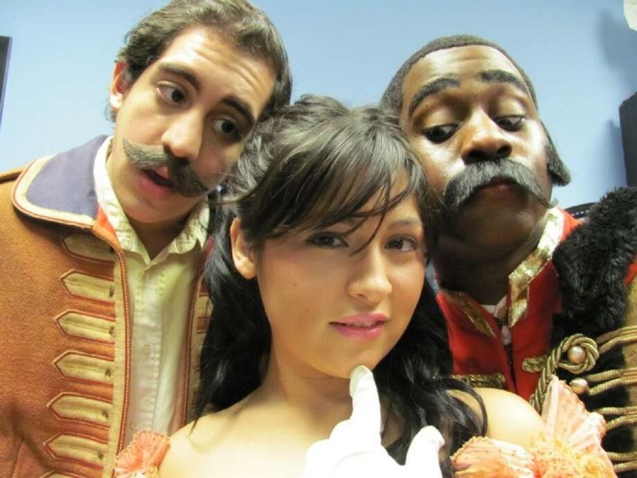 Raina Petkoff a starry eyed romantic, is torn between two suitors: her ideal soldier-hero, Sergius Saranoff, and a decidedly unheroic Swiss mercenary, Captain Bluntschli, in George Bernard Shaw's Arms and the Main, opening at HCC Central College. Pictured from left to right: Livingstion Denegre-Vaught Ecebiri as Bluntschli, Sherry Calderon as Raina and Joshua Echebiri as Sergius. (Photo by Ed Muth, submitted by HCC Central Fine Arts)