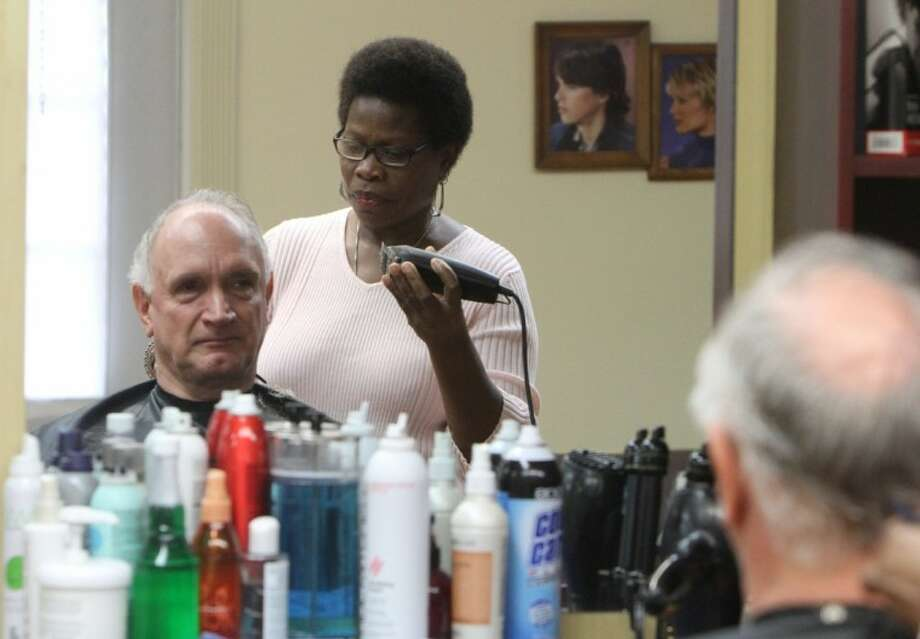 Madia Robertson gives Ed Hayman a trim at her hair salon in Shepherd. A Liberian immigrant, Madia has developed a loyal customer base and counts her regular customers as family. The Greater Shepherd Chamber of Commerce held a ribbon cutting at Quality Cuts by Madia on Saturday, Feb. 11. Photo: JASON FOCHTMAN