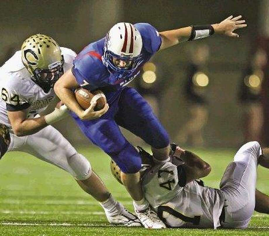 Oak Ridge quarterback Ryan Cyr tries to maneuver past Conroe's Patrick Webber (64) and Jeremy Schilhab (47) this past fall at Woodforest Bank Stadium. Cyr was one of 26 Montgomery County football players to earn academic all-state status. / The Courier