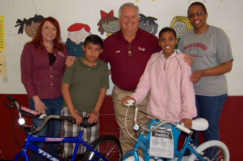 Jones Elementary School fourth grade student Pablo Sandoval and fifth grade student Breanna Davis both won a new bike just in time for spring break. National School Breakfast Week was celebrated in Waller ISD schools and 10 donated bikes were given away in a random drawing. Students' who ate breakfast at school during the week were eligible for the drawing. Elementary breakfast meals served during the week increased by 6 percent. Pictured from the left is Food Service Director April Pinkham, who coordinated the bike giveaway project, Pablo, Waller ISD Supt. Danny Twardowski, Breanna, and Principal Carol Bates.