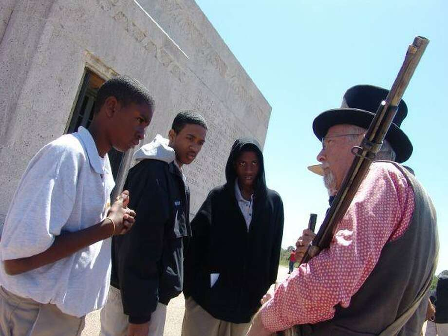 David Pomeroy (left) tells the story of Texas' independence to a group of students as they tour the San Jacinto Monument.