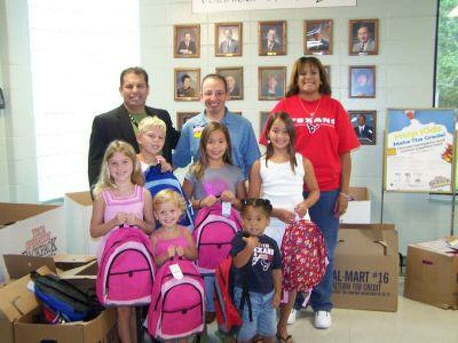The Wal-Mart in Fall Creek donated more than 100 backpacks to the Lake Houston Family YMCA Operation Backpack to make sure that kids in need were ready to start the new school year off on the right foot. Cezar Gonzalez, executive director of the Lake Houston Family YMCA; Joe Alvarez, Fall Creek Wal-Mart store manager; and Shari Reed, Wal-Mart Community Involvement coordinator, hand out backpacks to Maya Ditges, 7; Thomas Ditges, 10; Christina Cano, 7; Marissa Cano, 10; Chloe Ditges, 4; and Jaicon Anderson, 4.