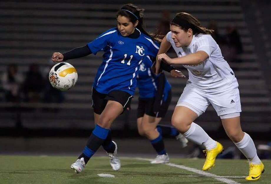 New Caney's Evelyn Santillan battles against Conroe's Chloe Sinclair during Tuesday night's match at Buddy Moorhead Memorial Stadium. / The Courier