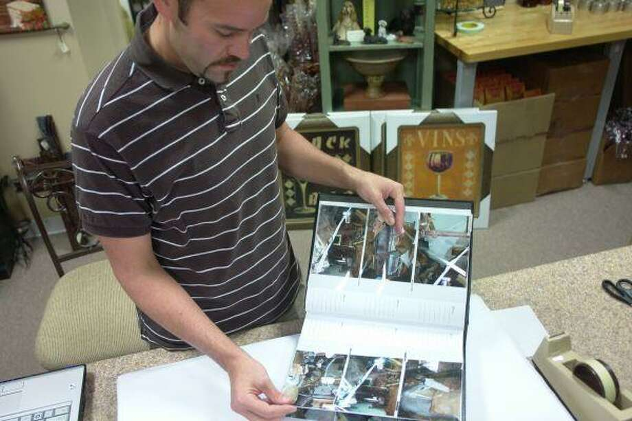 Mark McCarley looks through photos of his hurricane-damaged home, which he shared with Sean Lacoste and Eric Johnson. They resided in St. Bernard Parish, which was was completely destroyed after Hurricane Katrina. With nothing to lose, the three moved to Atascocita and opened their own gift boutique, Grace's Unique Gift Boutique.