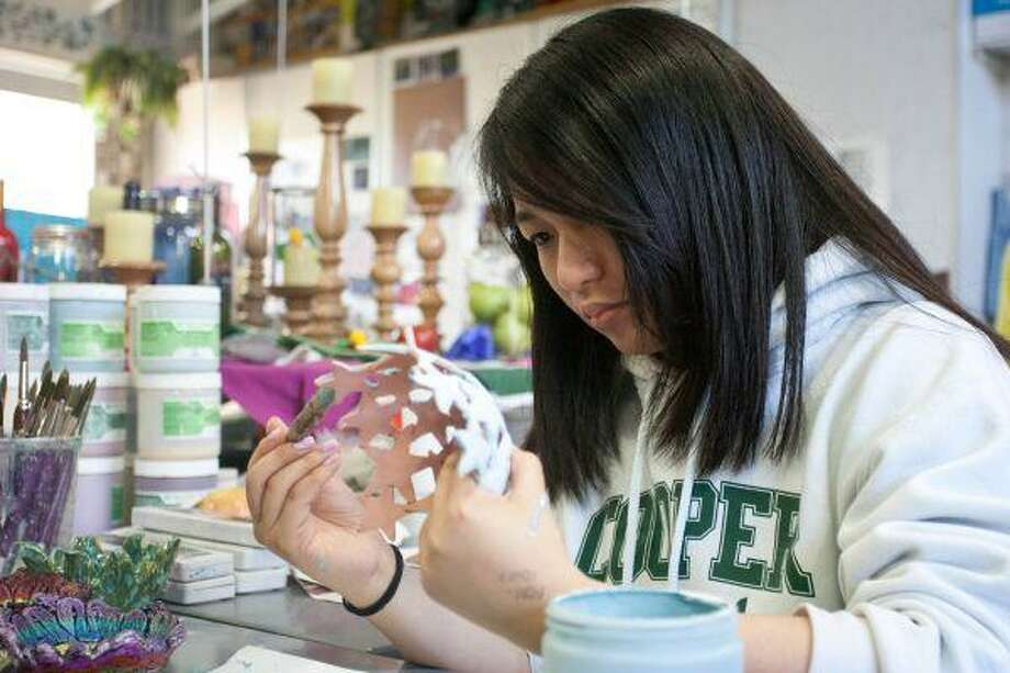 John Cooper School junior Tiffany Woo, 17, works on painting a bowl she created as part of the school's Empty Bowls Project. The bowls will be featured Saturday in a fundraiser to benefit the Interfaith Food Pantry. / The Courier