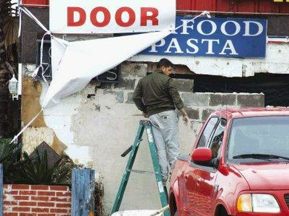 A crew makes repairs to the exterior of Baytown Seafood at the corner of West Main Street and Lee Drive following yet another oncoming vehicle. Restaurant owner Issara Mac says this will be the last time, annoucning plans to relocate the site of his seafood restaurant to a different spot on the same property.