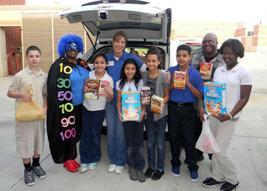 Pictured with donated food items are: (from left) Nathanial Juarez, Zero the Hero (who is actually kindergarten aide, Tangela Gunner), Ashley Chavez, Valerie Gutierrez, Ashlyne Steen, Michael Garcia, Branycia Mitchell; and (back row) Connie Esposito of the East Fort Bend Human Needs Ministry and Reginald Taylor, math specialist.