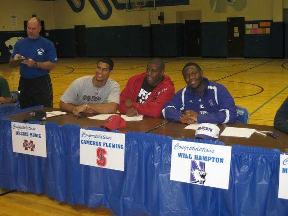 Cy Creek High seniors Archie Muniz (Mississippi State), Cameron Fleming (Stanford) and Will Hampton (Northwestern) signed their National Letter of Intent on Wednesday at Cy Creek High. The three linemen helped Cy Creek repeat as Class 5A-District 15 champions last fall. (Photo by Michael Sudhalter/THE SUN)