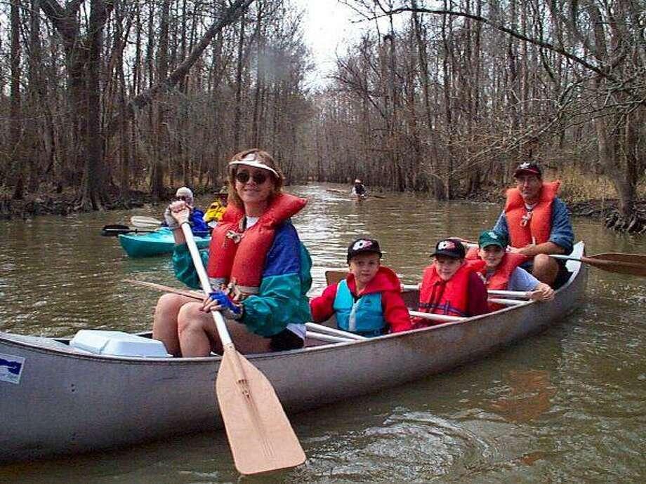 A family enjoys a canoe trip on Buffalo Bayou, the longest Paddle Trail in Texas.