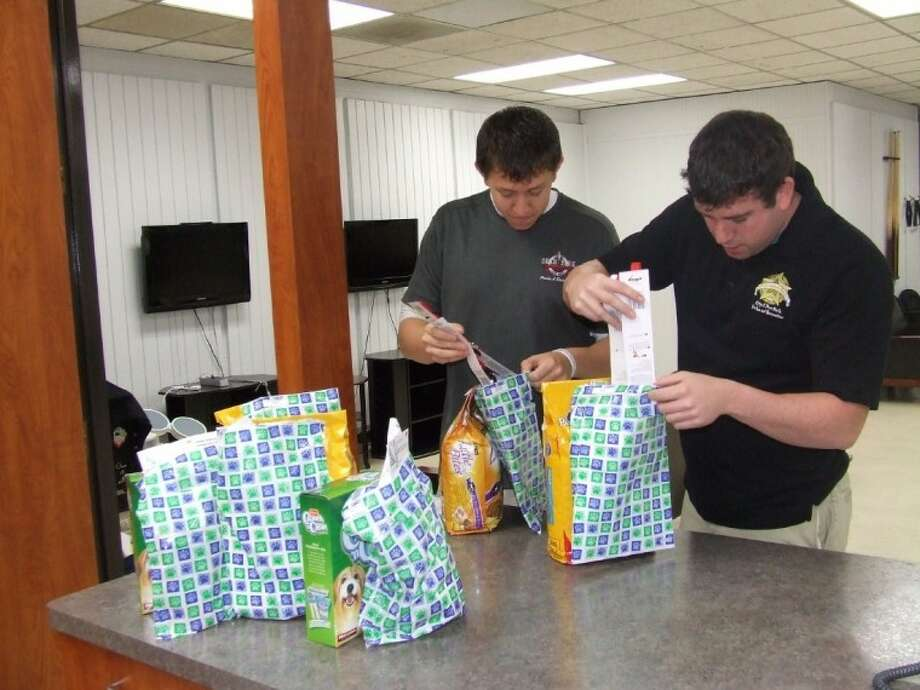Taylor and Ryan McBride fill bags of pet supplies to be delivered to senior citizens in Deer Park as part of the newly formed Animeals on Wheels program. Photo: Jeri Martinez