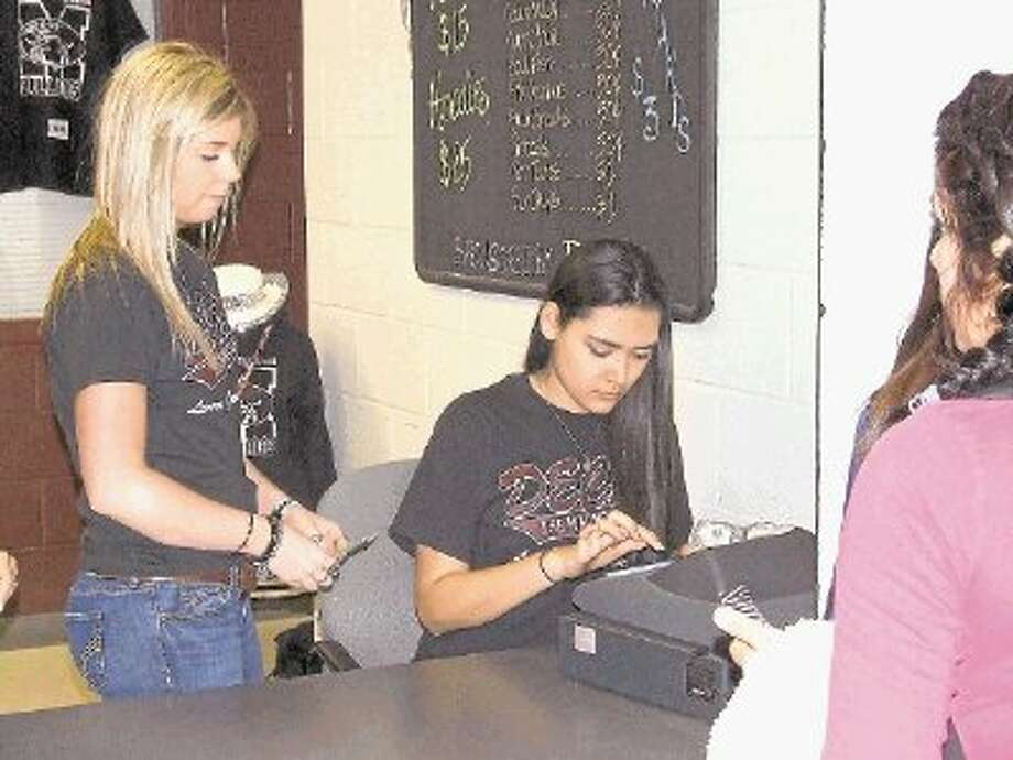 Katy Moss, left, and Brookelyn Felan work the cash register at The Dog Den at Magnolia High School. The store is run by DECA students and helps to teach them entreprenuership. Photo: Lindsey Vaculin / @WireImgId=2615320