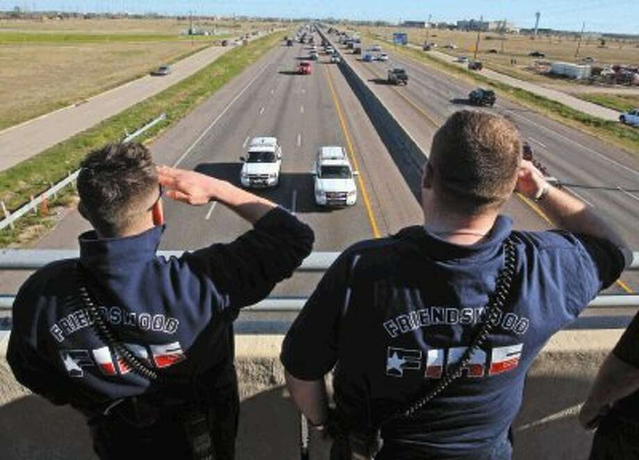 Friendswood and Forest Bend Firefighters stand along the Gulf Freeway at El Dorado in Houston Texas on Sunday February, 17 2013 as the procession for Bryan Firefighter Lt. Greg Pickard, 54 who died at UTMB Galveston after sustaining injuries at a fire in Bryan Texas is escorted back to Bryan. Photo: Kar B Hlava / Conroe Courier