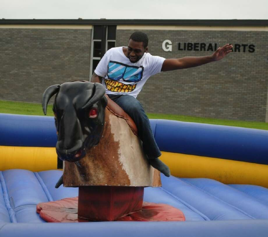 ACC student Jarrell Campbell tries to hang on while riding a mechanical bull outside the Student Center on Thursday, February 23. Photo: ACC