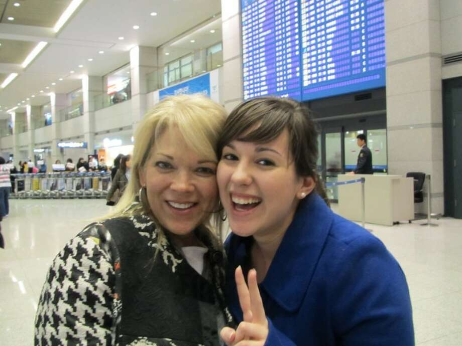 Amy White Jelonek, left, and her daughter, Alex White, celebrate on arrival in Seoul, South Korea after just missing the Japanese earthquake.