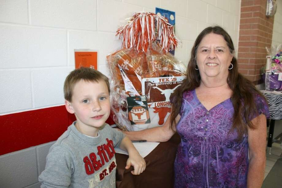 Connor Carpenter, left, and his grandmother Dedria Menge bid on a Texas Longhorn memorabilia basket at the Kimmie M. Brown Elementary Class Creation Dinner and Silent Auction. Carpenter said that he wants to attend UT Austin when he graduates from Dayton High School.