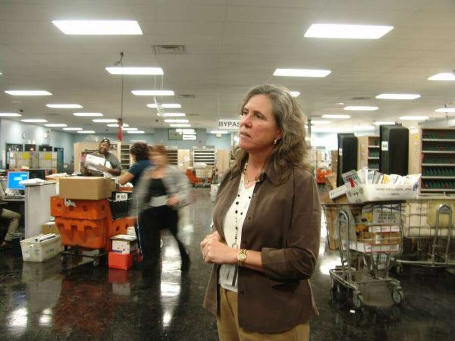 Postmaster Karen Parson gives Chamber of Commerce members a behind-the-scenes look at the Cullen Blvd. post office last week.