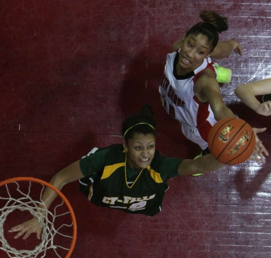 Cy-Falls' Loryn Goodwin (32) goes up for a rebound over North Shore's Adriiana Jackson (11) during the girls Region III-5A regional semifinals game at the M.O. Campbell Education Center on Feb. 24. Photo: Jason Fochtman