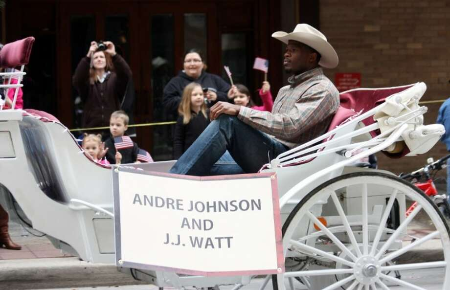 Andre Johnson of the Houston Texans, co-marshal of the Houston Livestock Show and Rodeo Parade along with J.J. Watt, rides in a horse-drawn carriage in the parade downtown Saturday.
