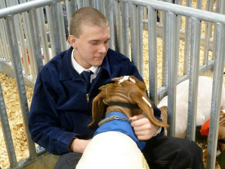 Klein Collins student Matthew May calms his goat before the auction.