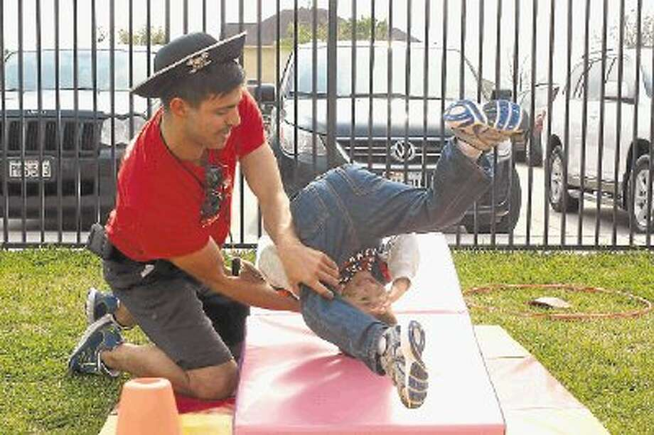 Luke Speller takes a tumble backwards with the help of Coach Jo Rodgers during the Goddard School 25th birthday celebration in Friendswood. Photo: KIRK SIDES / © 2012 Kirk Sides/Houston Community Newspapers
