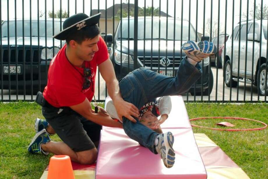 Luke Speller takes a tumble backwards with the help of Coach Jo Rodgers during the Goddard School 25th birthday celebration in Friendswood. Photo: KIRK SIDES
