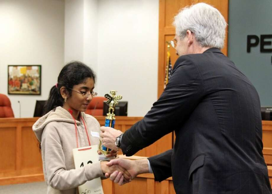 Shobha Dasari accepts the championship trophy from Superintendent Dr. John Kelly after winning the Pearland ISD district Spelling Bee Wednesday, Feb. 22. Photo: Kirk Sides