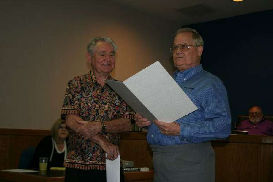 """Mayor Donnie McMannes, right, reads a proclamation in honor of Edgar W. """"Sonny"""" Robbins III who was mayor of Humble from 1967 to 1971. The proclamation was given to Robbins after the Humble City Council meeting April 23."""