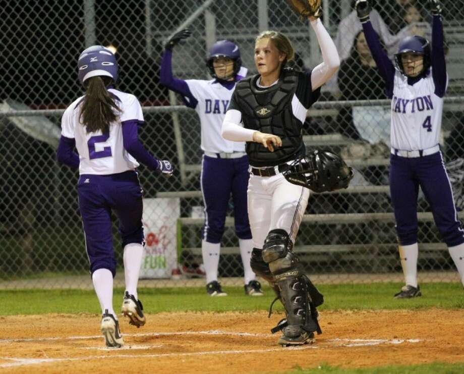 Dayton's Ravin Wilson scores a first inning run for the Lady Broncos. Also pictures are Dayton's (4) Lyndsey Harryman, Samantha Scott and Huffman catcher Loren Dempsey.