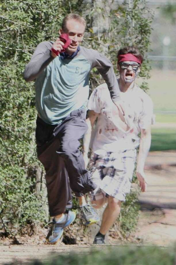Blue team member Tim Mousel gets chased by red team member Zach Kneuven, dressed as a zombie, as he runs away with the red team flag during a zombie version of Capture the Flag at Lone Star College-Montgomery on Tuesday. The Learning Networks and Kinesiology Club organized the event for students, faculty, staff, and community members to benefit the Montgomery County Food Bank. Players and spectators were encouraged bring two canned food items and dress like a zombie.