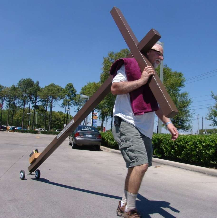 "Joe Gaston continues the ""Jesus is no fool"" walk from Pasadena to La Marque carrying his cross with him."