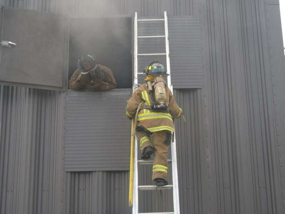 Recruits of the AVFD fire academy practice a ground ladder rescue during a recent live burn scenario. This type of rescue is common in residential fires when occupants can be trapped in living spaces and sleeping quarters. Perfecting this type of rescue operation is essential to life safety protection, said instructor Lt. Brian Mulligan.