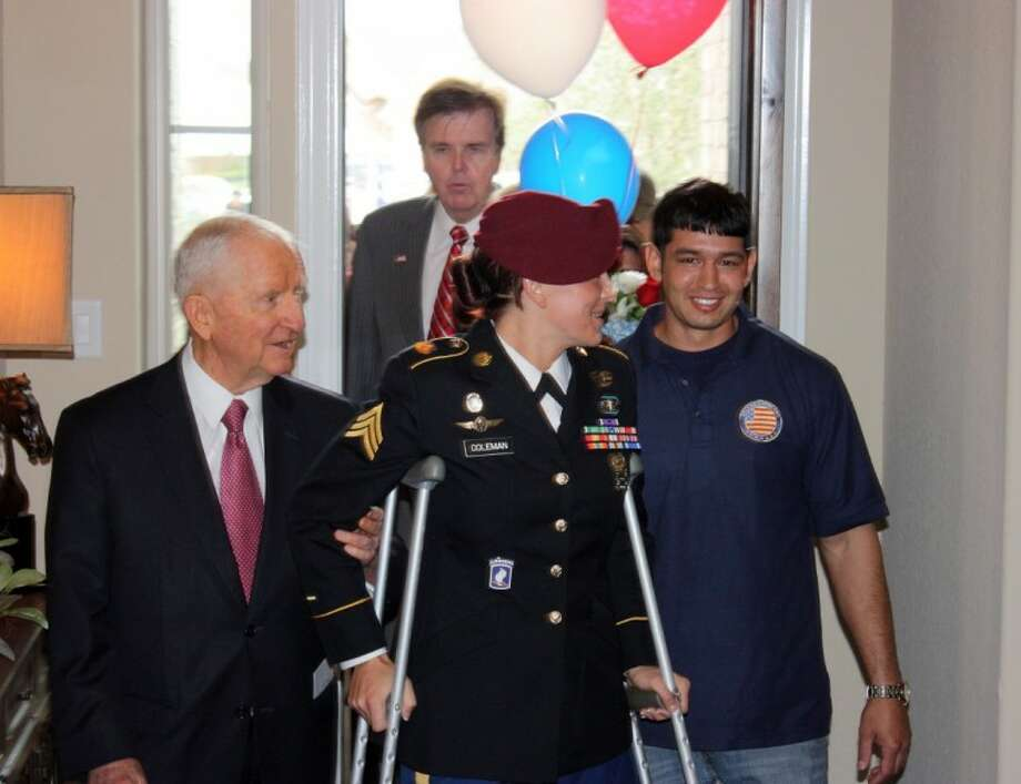 Sgt. Kendra Coleman and her husband Anthony Garza enter their new home for the first time, escorted by H. Ross Perot Sr. Following behind is State Sen. Dan Patrick.